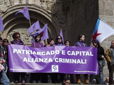 Galician protestors in Spain, Feministas en resistencia (Feminist resistence) hold a banner on church steps that reads: Patriarcado e capital alianza criminal (Patriarchy and the capital alliance are criminal), Spain, 2011 (Source: Wikimedia Commons)